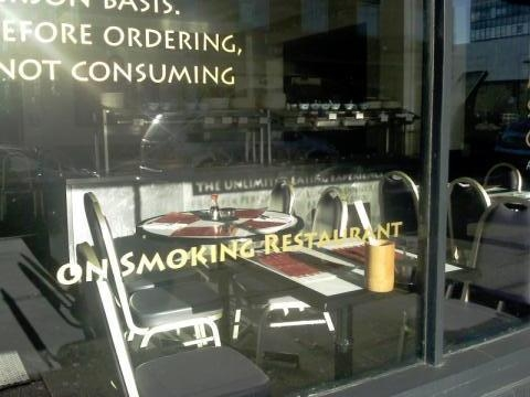 Text on the window of a restaurant reads ''ON SMOKING RESTAURANT''
